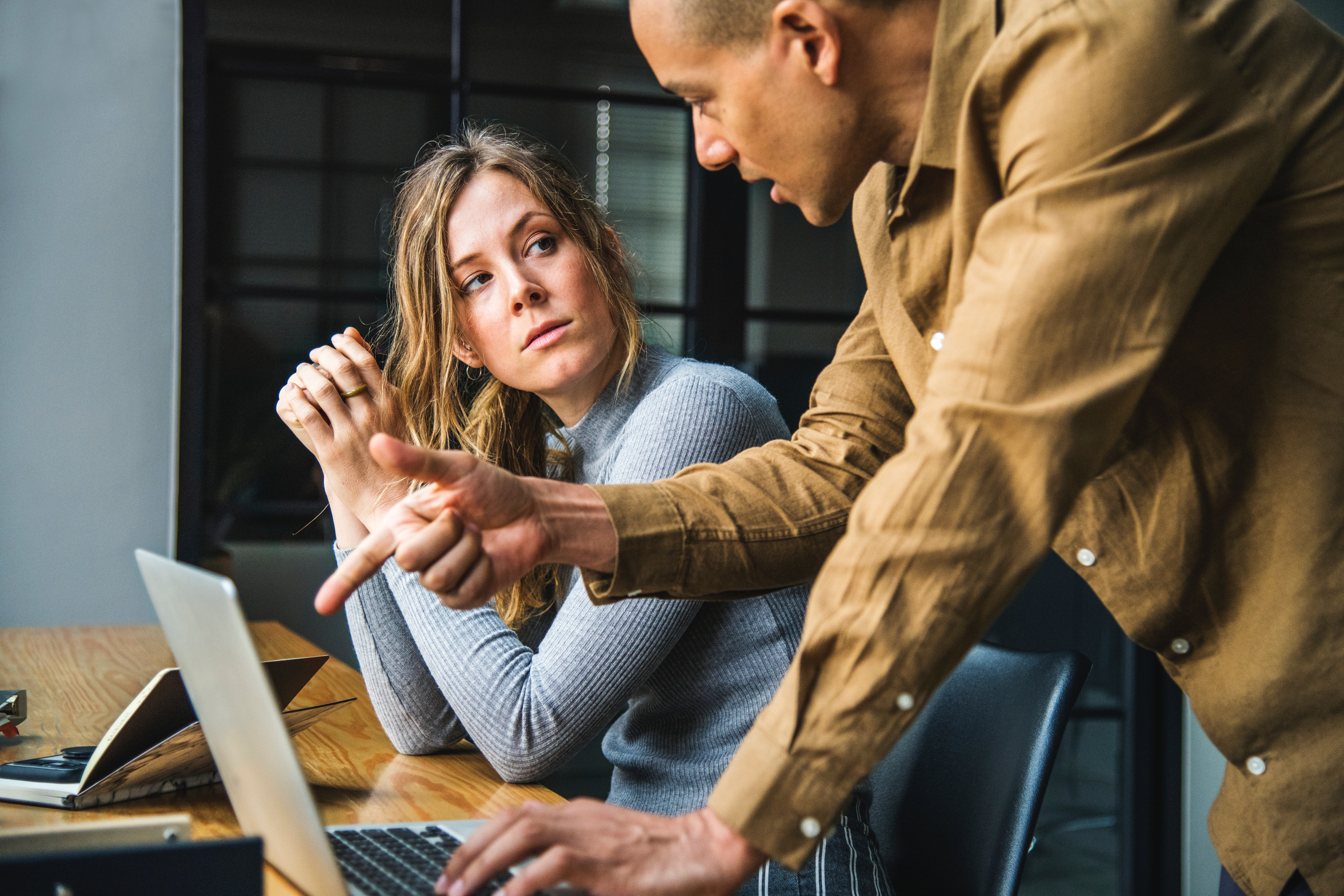 man showing woman how to do something at the laptop