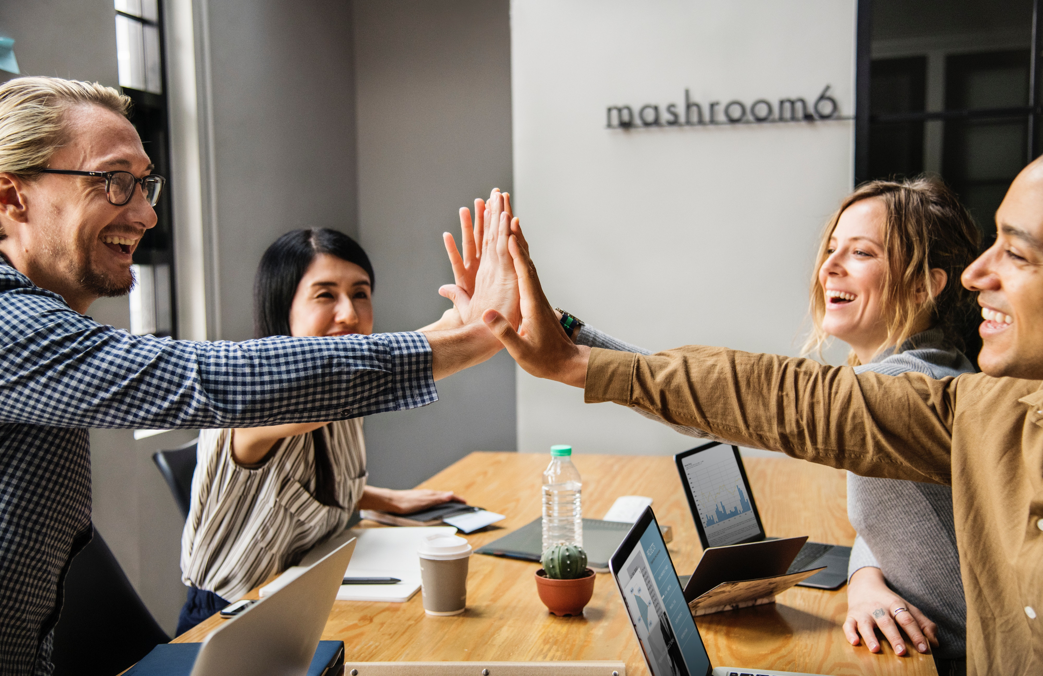 businessmen and women high fiving