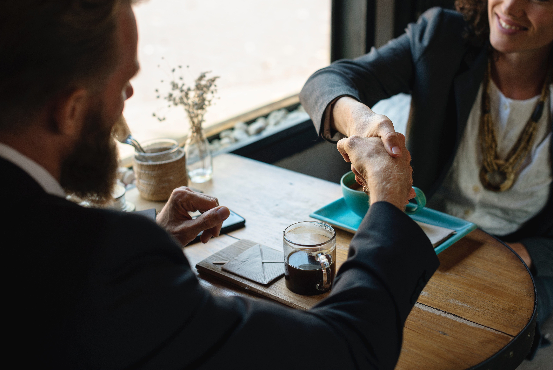 man and woman handshake over table