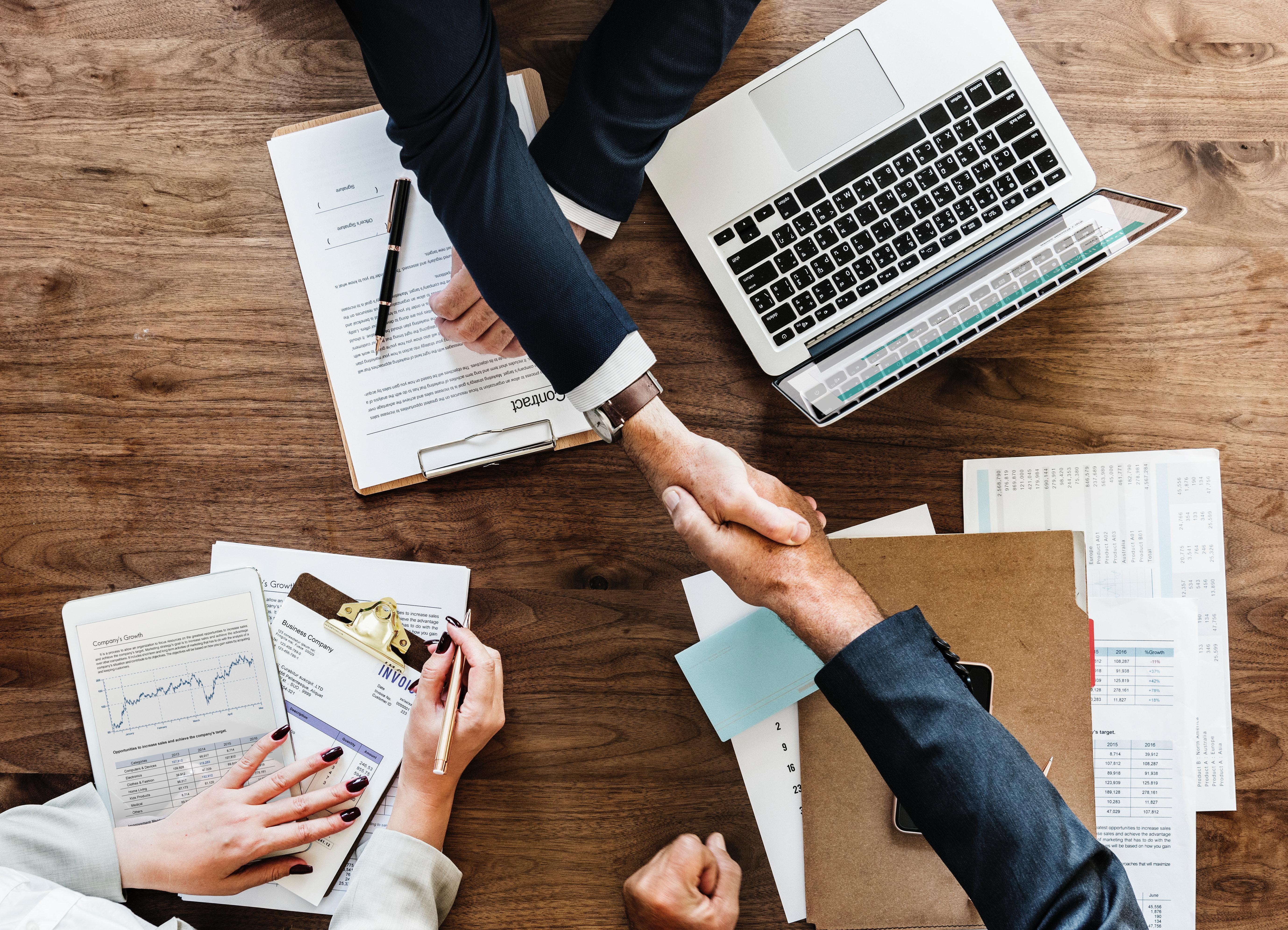 businessmen handshaking over table